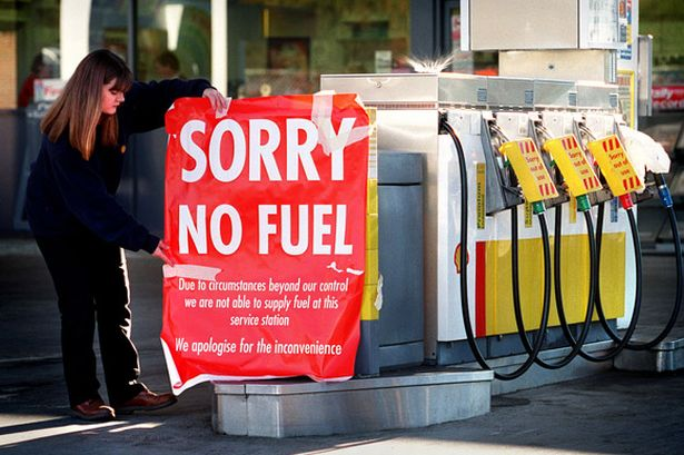 Garage worker Nicole Tuxford puts up a sign at a Shell petrol station in Dunblane.jpg